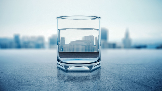 A clean glass of water with New York City in the background.