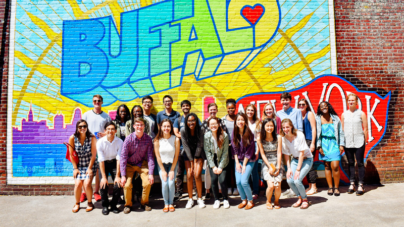 Students stand in front of a mural that reads Greetings from Buffalo