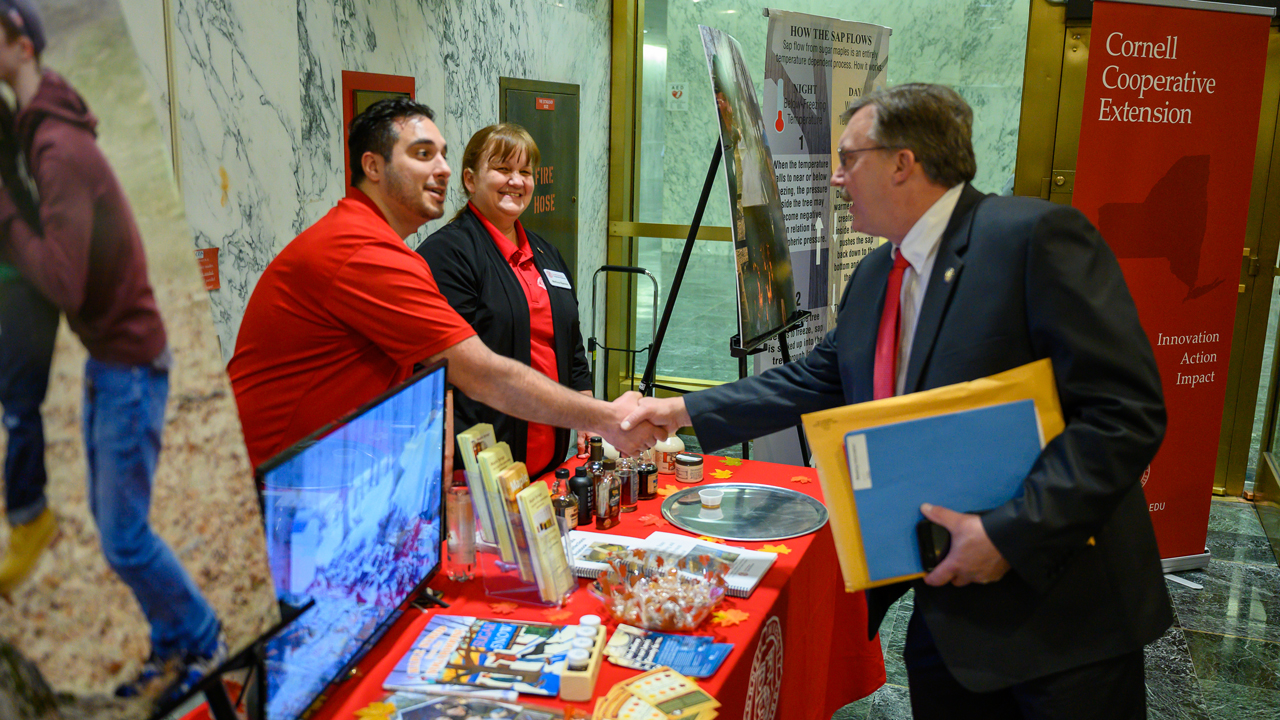 Legislator meets CCE employees at their table in the capitol building