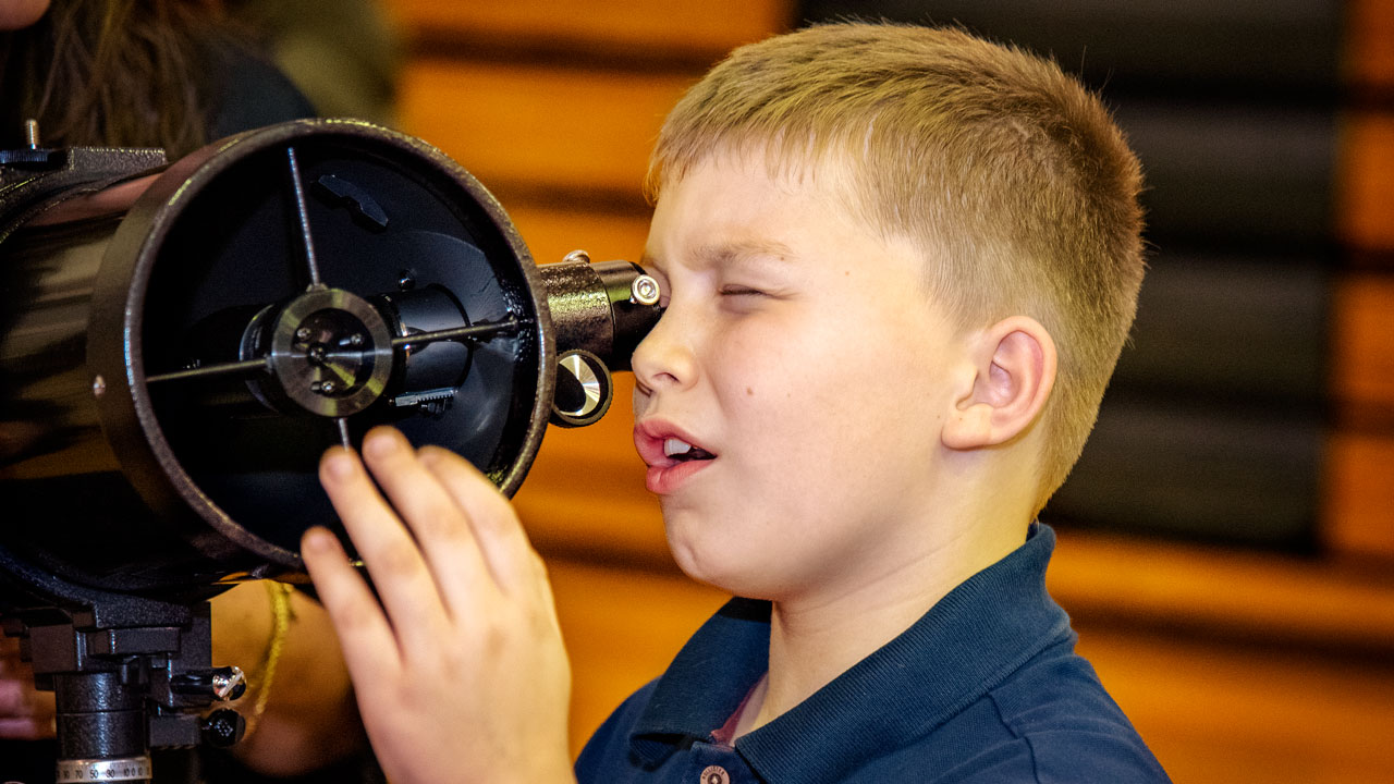A young boy looks into a telescope.